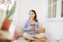 Beautiful young woman relaxing and laying down on an exterior bed on a home terrace garden and reading a magazines while on. Holiday royalty free stock images
