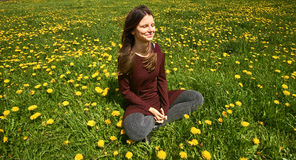 Beautiful young woman relaxing on a meadow with many dandelions in the spring sun. Smiling with copyspace. Stock Images