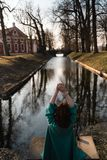 Beautiful young woman relaxing near a canal river in a park near the palace in Rundale, Latvia, 2019 stock photos