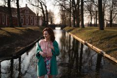 Beautiful young woman relaxing near a canal river in a park near the palace in Rundale, Latvia, 2019 royalty free stock image