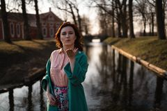 Beautiful young woman relaxing near a canal river in a park near the palace in Rundale, Latvia, 2019 stock photography