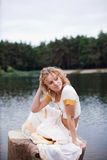 Beautiful young woman relaxing near the lake. In a park Stock Photo