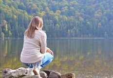 Beautiful young woman relaxing near a lake. Beautiful young woman relaxing on near a lake in autumn landscape Royalty Free Stock Image