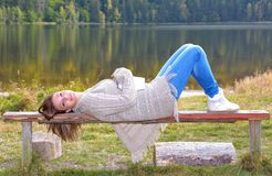 Beautiful young woman relaxing near a lake. Beautiful young woman relaxing on a bank near a lake Royalty Free Stock Images