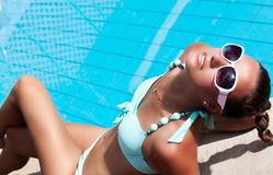 Beautiful young woman relaxing near the swimming pool Royalty Free Stock Photo
