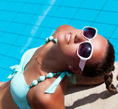 Beautiful young woman relaxing near the swimming pool Royalty Free Stock Photos