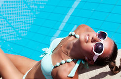Beautiful young woman relaxing near the swimming pool Royalty Free Stock Images