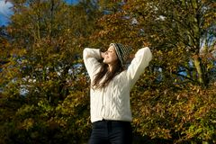 Beautiful young woman relaxing outdoors and enjoying a sunny autumn day Royalty Free Stock Photos