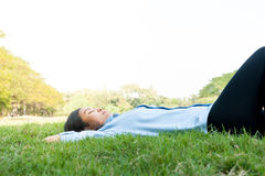 Beautiful young woman relaxing at the park,in green grass meadow Royalty Free Stock Image