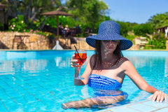 Beautiful young woman relaxing in pool with Stock Images