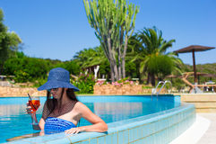 Beautiful young woman relaxing in pool with Royalty Free Stock Image