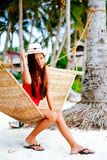 Beautiful young woman relaxing on rattan hammock on the white sand beach during travel vacation Royalty Free Stock Photography