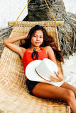 Beautiful young woman relaxing on rattan hammock on the white sand beach during travel vacation.  Royalty Free Stock Photo