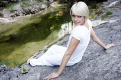Beautiful young woman relaxing on a rock Royalty Free Stock Photo