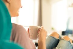 Young woman relaxing on the sofa at home, watching tv and enjoying coffee royalty free stock photos