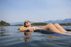 Beautiful young woman relaxing in the summer sun on the lake Royalty Free Stock Photos
