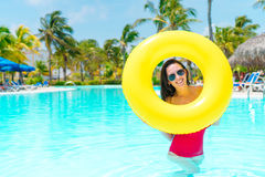 Beautiful young woman relaxing in swimming pool. Girl in outdoor pool at luxury hotel with inflatable rubber circle Royalty Free Stock Photos