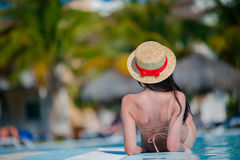 Beautiful young woman relaxing in swimming pool. Happy girl in outdoor pool at luxury hotel Royalty Free Stock Photos
