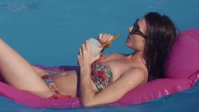 Beautiful young woman relaxing in swimming pool in summer, lying on inflatable Lounge in sunglases Summer time. She stock video footage