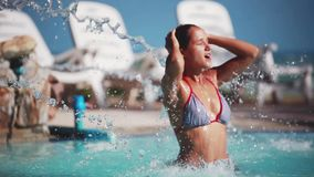 Beautiful young brunette woman relaxing in a swimming pool. Woman under pool waterfall. 1920x1080, hd. Beautiful young woman relaxing in a swimming pool. Woman stock footage