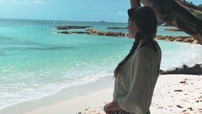 Beautiful young woman relaxing on tropical beach. Pretty girl on tropical beach enjoying a beautiful view of the open sea stock video