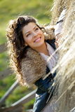 Beautiful young woman relaxing under a hay stack Stock Image
