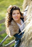 Beautiful young woman relaxing under hay stack in autumn Royalty Free Stock Image