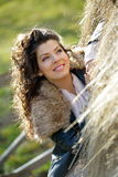 Beautiful young woman relaxing under hay stack in autumn Stock Photos