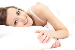 Beautiful young woman relaxing in white bedding Stock Photography
