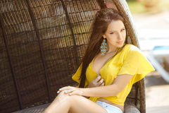 Beautiful young woman relaxing on wooden plank bed near pool Royalty Free Stock Photography