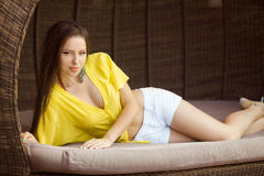 Beautiful young woman relaxing on wooden plank bed near pool Stock Image