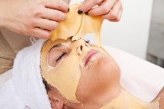 Beautiful young woman remove  facial mask Stock Image