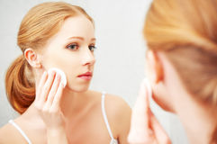 Beautiful young woman removes makeup with face skin Royalty Free Stock Photos