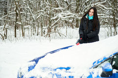 Beautiful young woman removing snow from her car Stock Images