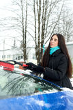 Beautiful young woman removing snow from her car Royalty Free Stock Photos