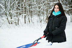 Beautiful young woman removing snow from her car Royalty Free Stock Photography