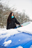 Beautiful young woman removing snow from her car Stock Photo