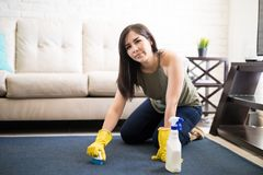 Upset and tired woman cleaning carpet at home. Beautiful young woman removing stain from carpet looking at camera Royalty Free Stock Photography