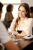 Beautiful young woman in a restaurant. Beautiful young woman smiling at her partner in a restaurant Royalty Free Stock Images