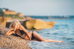 A beautiful young woman resting on the beach. Royalty Free Stock Image