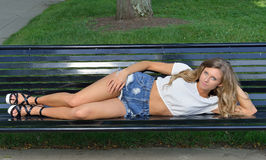 Beautiful young woman resting on park bench Royalty Free Stock Image