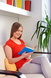 Woman resting on sofa and reading the book Stock Images