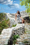 Beautiful young woman resting on a stone wall Royalty Free Stock Image