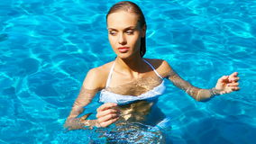 Beautiful young woman resting in the swimming pool