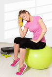 Beautiful young woman resting after tiring workout. Light background Stock Photos