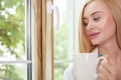 Beautiful young woman is resting on windowsill Stock Images
