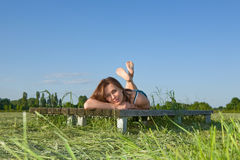 Beautiful young woman rests on the green grass Stock Images