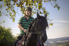 Beautiful young woman rides her black Horse Royalty Free Stock Photography
