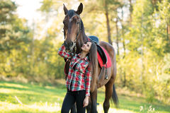 Beautiful young woman rides on a horse outdoor Royalty Free Stock Image
