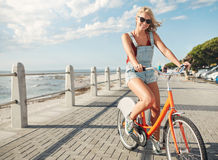 Beautiful young woman riding bicycle on seaside road Royalty Free Stock Images